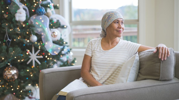 woman in head scarf sitting beside Christmas tree