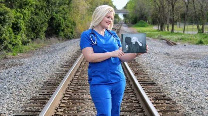 cancer survivor, Crystal Zunino, standing on a rail road track holding a picture of herself during treatment