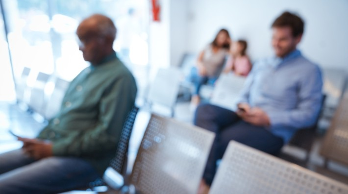 out of focus image of people sitting in a doctor's waiting room
