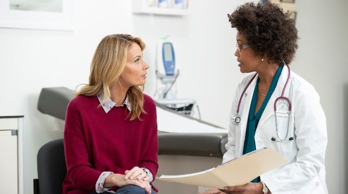 female doctor talking to female patient in exam room