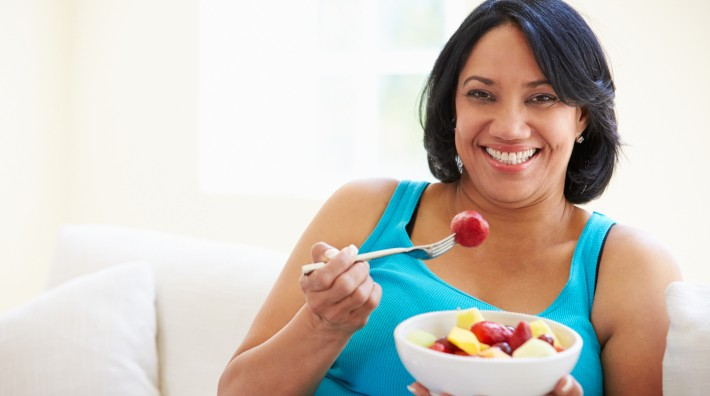 happy woman sitting on couch eating a bowl of fruit