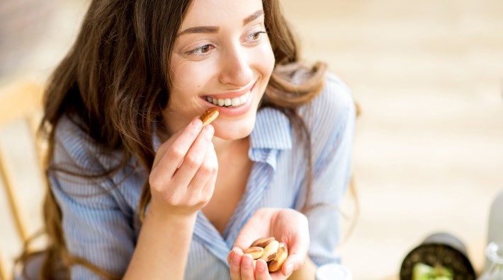 Closeup view from above of a woman eating brazil nuts