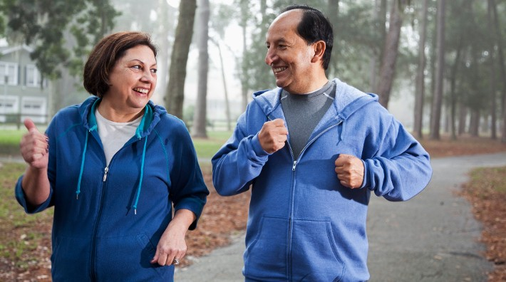 middle aged Hispanic couple walk for exercise in park